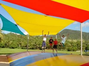Teens playing on an outdoor jumping pillow with cover and shade